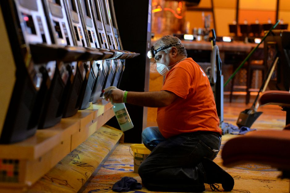 A Mohegan Sun staff member disinfects a row of slot machines as they prepare for reopening sometime in the coming weeks after shutting down on March 17 due to the COVID-19 pandemic. The casino is undergoing a floor-to-ceiling cleaning to ensure the safety of casino goers once they return. | Cloe Poisson, The Connecticut Mirror