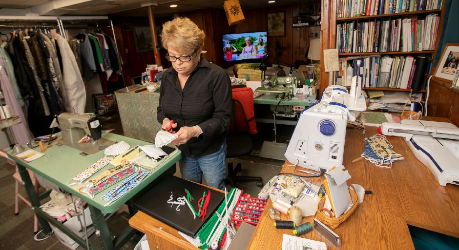 Patricia Longobardi, owner of Sewing by Patricia in Wallingford, trims a coffee filter which she inserts into fabric masks she