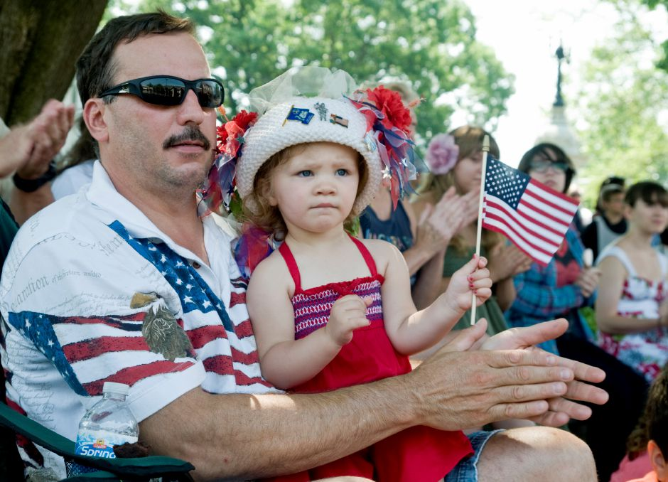 From left: Tony Casale watches the Memorial Day parade with his granddaughter, Morgan Allan,2, on the Town Green in Southington, May 28, 2012. Allan wore a festive hat made by her grandmother, Karen Casale. (Sarah Nathan/Record-Journal)