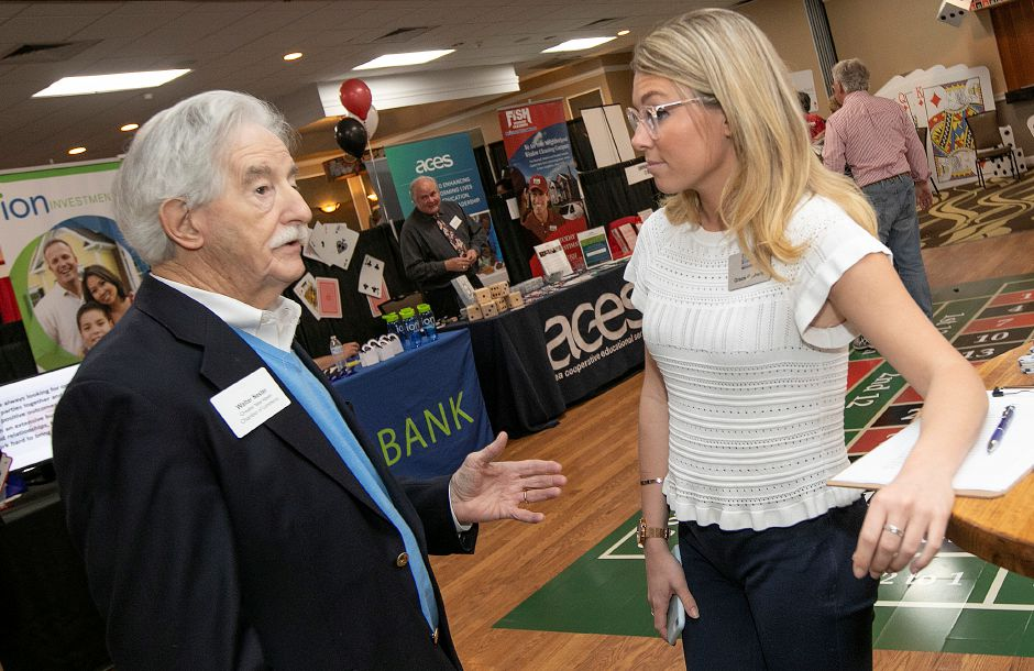 Walter Nester, business development executive for the Greater New Haven Chamber of Commerce, talks with Grace Gothers, Events & Communications Coordinator and Director of PULSE at Greater New Haven Chamber of Commerce, during the casino-themed Quinnipiac Chamber of Commerce Annual Business Showcase at the Best Western in North Haven, Thurs., Apr. 4, 2019. Dave Zajac, Record-Journal