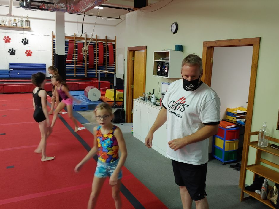Wes Norris, co-owner of CATS Gymnastics in Cheshire, instructs one of his students on Friday, July 31. John Rook/Cheshire Herald