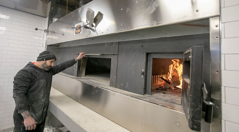 George Constanti, co-owner of Fuoco, checks a coal-fired brick oven after firing it up for the first time at the new pizza business under construction at 461 W. Main St., Cheshire, Mon., Feb. 10, 2020. Dave Zajac, Record-Journal
