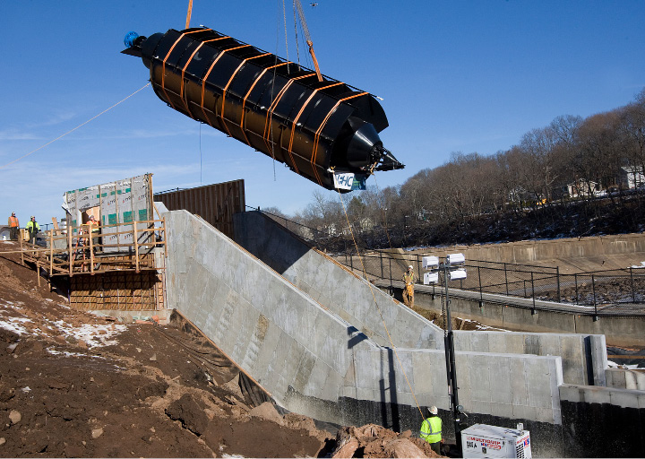 A 20-ton, 35-foot-long metal screw is lowered into place by crane at Hanover Dam in South Meriden on Tuesday. The Archimedes screw, named for the ancient Greek scientist credited with its invention, is the first of its kind installed in the U.S.  | Dave Zajac, Record-Journal