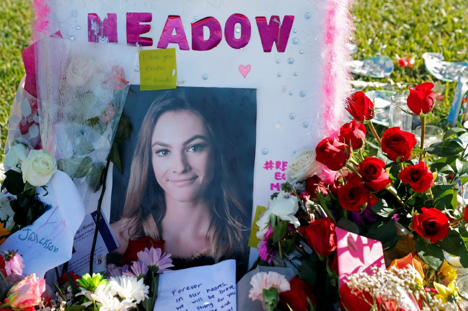 This Feb. 17, 2018 photo shows a photo of Meadow Pollack, one of the seventeen victims who was killed in the Wednesday, Feb. 14, 2018, shooting at Marjory Stoneman Douglas High School, sits against a cross as part of a public memorial, in Parkland, Fla. Nikolas Cruz, a former student, was charged with 17 counts of premeditated murder on Thursday. (AP Photo/Gerald Herbert)