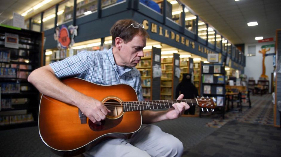 Left: The Music Shop store manager Scott Mulrooney tunes and plays a guitar Tuesday that