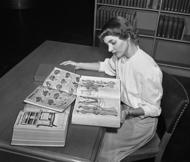 FILE - In an undated file photo, Ruth Parrington, librarian in the art department of the Chicago Public Library, studies early Sears Roebuck catalogs in the library