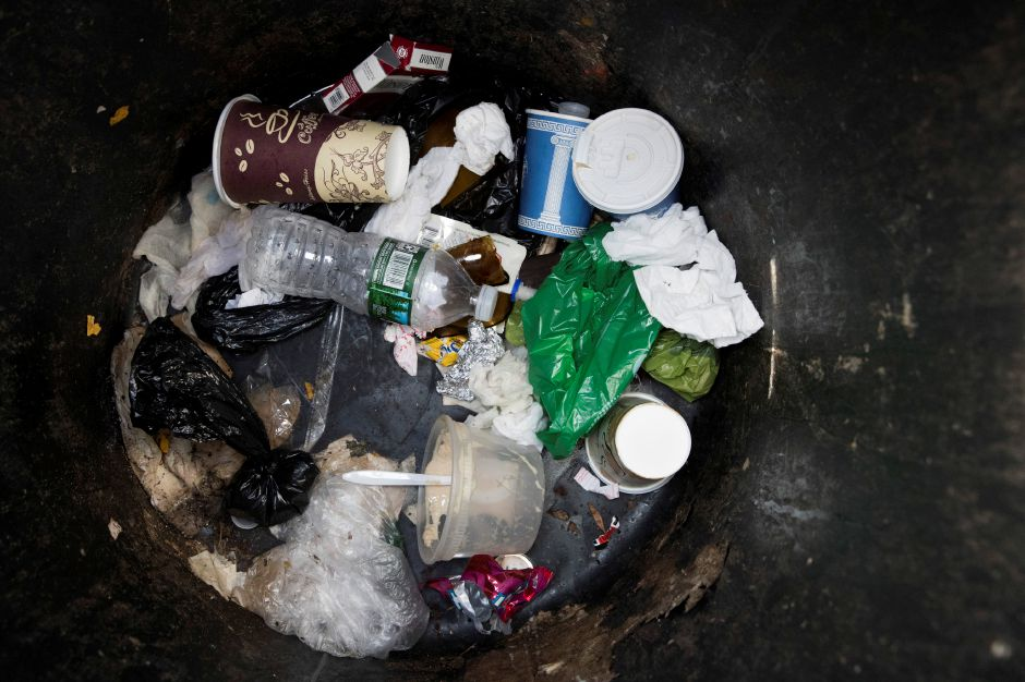 A plastic water bottle and plastic bags are seen discarded with other garbage in a corner trash can in the East Village neighborhood of Manhattan, Wednesday, March 27, 2019 in New York. Two New York lawmakers say Wednesday that they