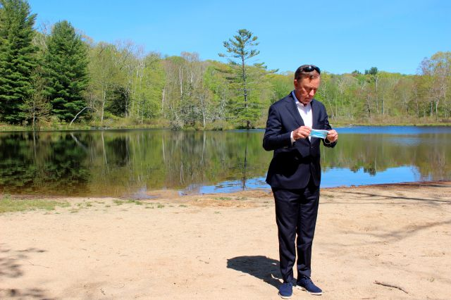 Connecticut Gov. Ned Lamont prepares to put on a face mask at Gay City State Park in Hebron, Conn. on Thursday May 21, 2020. The governor held his daily COVID-19 briefing for the media at the park in advance of the Memorial Day weekend. (AP Photo/Pat Eaton-Robb)