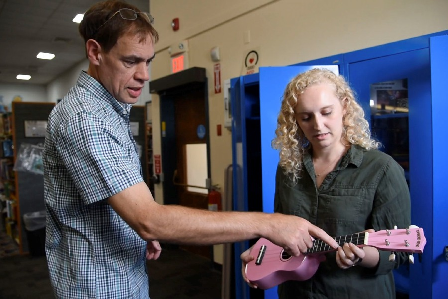 The Music Shop store manager Scott Mulrooney shows Record-Journal reporter Bailey Wright how to play a few chords on a pink ukelele at the Southington Public Library on Tuesday, August 26, 2019. The ukelele is one of about a dozen instruments that are newly available to borrow at the library. | Bailey Wright, Record-Journal