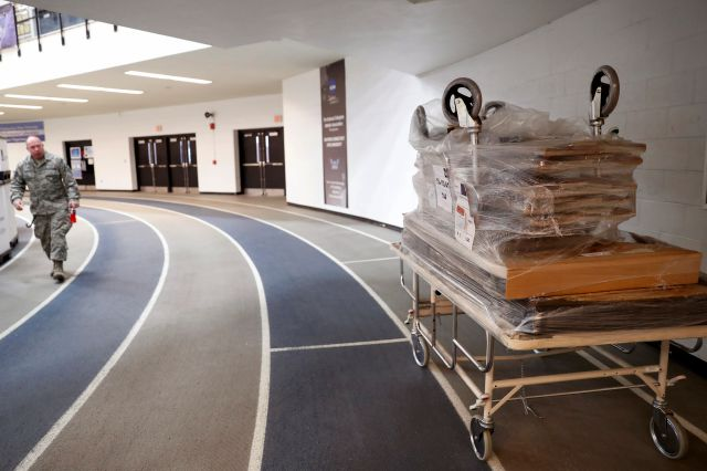 Hospital gurneys are stacked up, right, on an indoor track at Southern Connecticut State University
