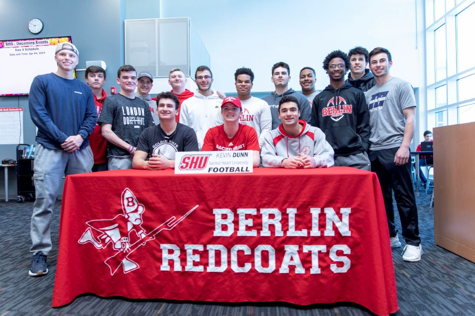 Kevin Dunn, center in red, was one of three Berlin High School athletes who signed copies of their letters of intent to move onto college level sports. A ceremony was held for the three at BHS on April 4, 2019. | Devin Leith-Yessian/Berlin Citizen