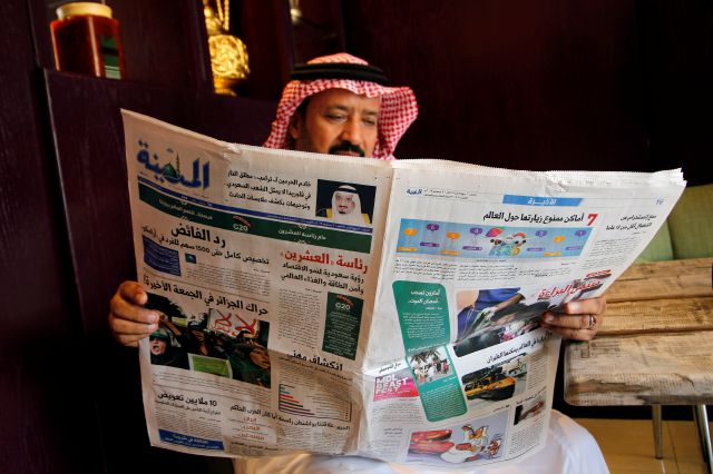 A man reads the daily Al-Madina newspaper fronted by a picture of Saudi King Salman at a coffee shop in Jiddah, Saudi Arabia, Saturday, Dec. 7, 2019. U.S. law enforcement officials were digging into the background of the suspected Florida naval station shooter Friday, to determine the Saudi Air Force officer