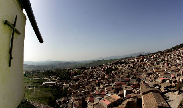 "FILE -- In this file photo taken on April 24, 2006, a crucifix towers over Corleone, Italy.The Sicilian town of Corleone, made famous by the fictional Mafia clan in ""The Godfather,"" has ordered schools closed and a limited lockdown after a spate of coronavirus infections were tied to a big wedding there last week. (AP Photo/Gregorio Borgia)"
