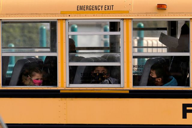 FILE - In this Thursday, Nov. 19, 2020, file photo, elementary school students sit on board a school bus after attending in-person classes at school in Wheeling, Ill. The latest federal relief package includes $81 billion that began flowing to states in late March 2021 with the goal of helping schools reopen quickly. The only problem is many of the school districts