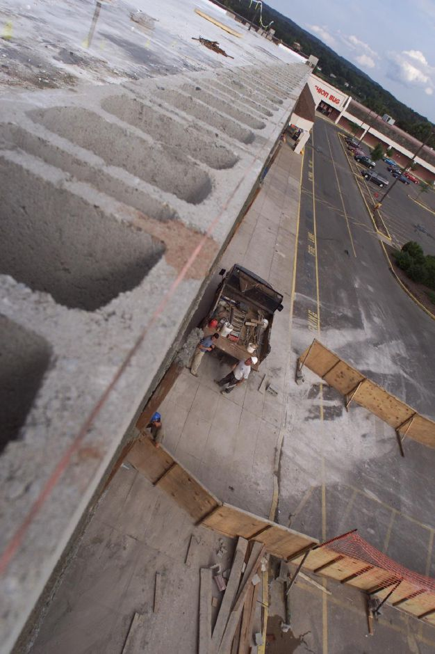 Looking down off of the roof under construction at the Townline Square in Meriden Aug. 4, 2000, workers clean the worksite in front of the new building.
