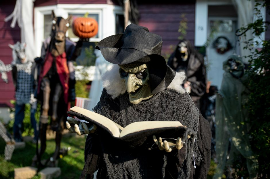 A witch and her grimoire are one of several figures in a Wallingford family