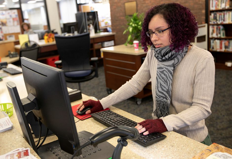 Frances Rosario, library clerk, works at the front desk at the Meriden Public Library, Mon., Dec. 2, 2019. Dave Zajac, Record-Journal