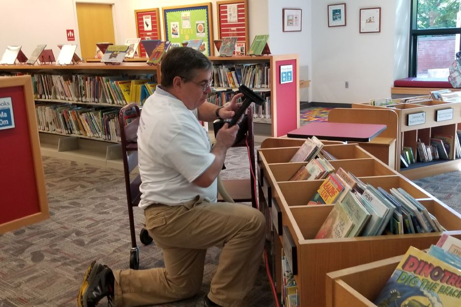 Mark Davis, Wallingford Rotary Club, vacuums bookcases at the Wallingford Public Library during the United Way Day of Caring Sept. 17, 2019. | Jeniece Roman, Record-Journal.