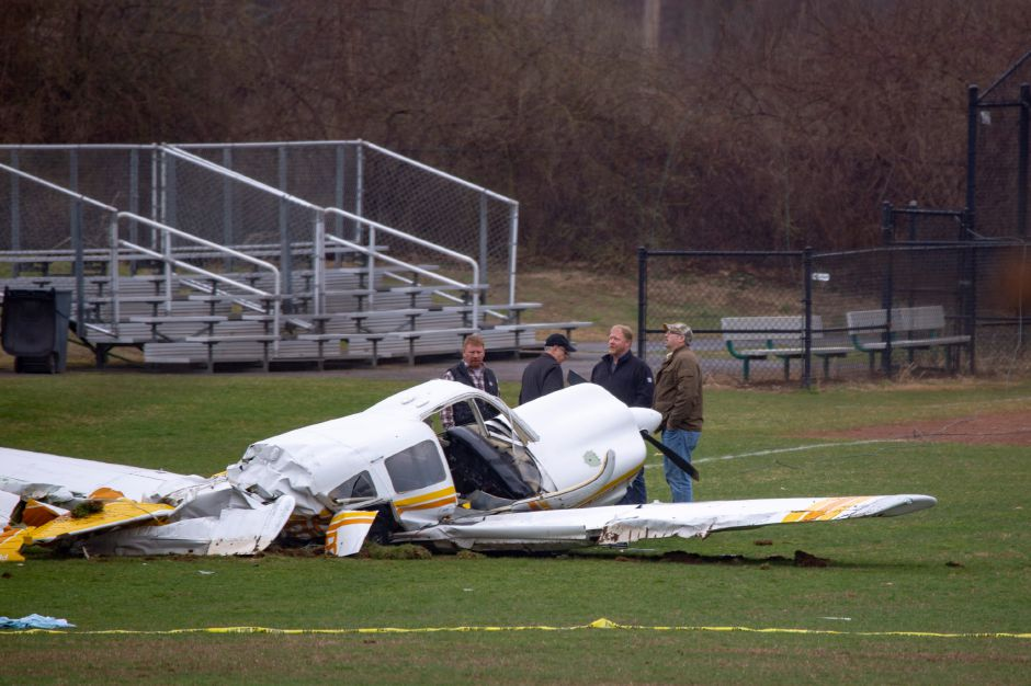 Officials look up towards the nearby power lines while looking over a plane crash on the ball fields at Wilcox Technical High School April 12, 2019. | Richie Rathsack, Record-Journal