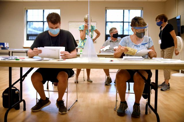Volunteers count mail-in ballots on Primary Day, Tuesday, Aug. 11, 2020, in Glastonbury, Conn. (AP Photo/Jessica Hill)
