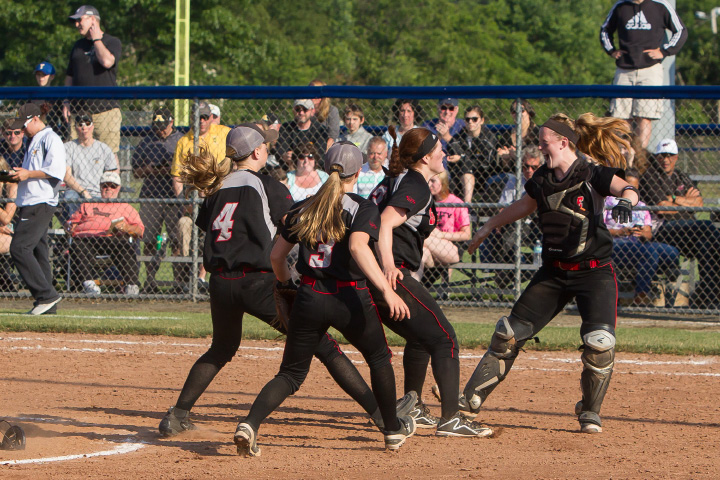 Cheshire catcher Megan Hodgdon and teammates rush pitcher Abby Abramson on the mound after the final out was recorded in Saturday