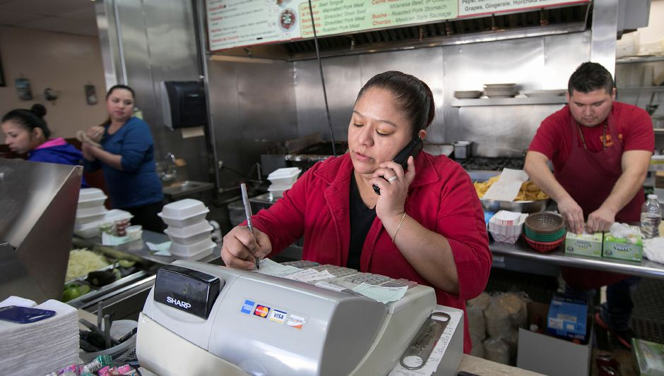 Waitress Luisa Peralto helps a customer with an order while working the lunch rush at Tacos Mi Nacho on Broad Street in Meriden in January. File photo, Record-Journal