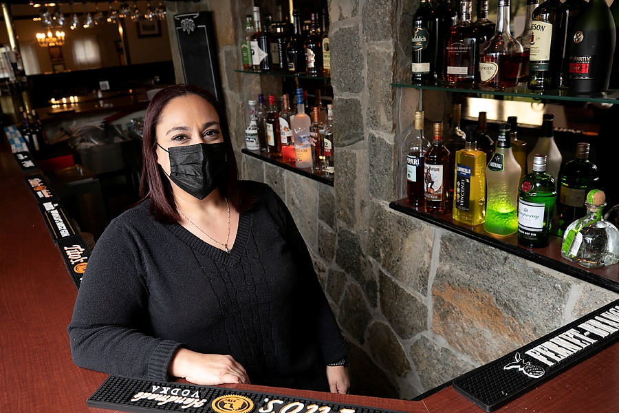 Manager Maria Riopel poses for a photo wearing a protective face mask at the bar inside  Laskara Restaurant in Wallingford.