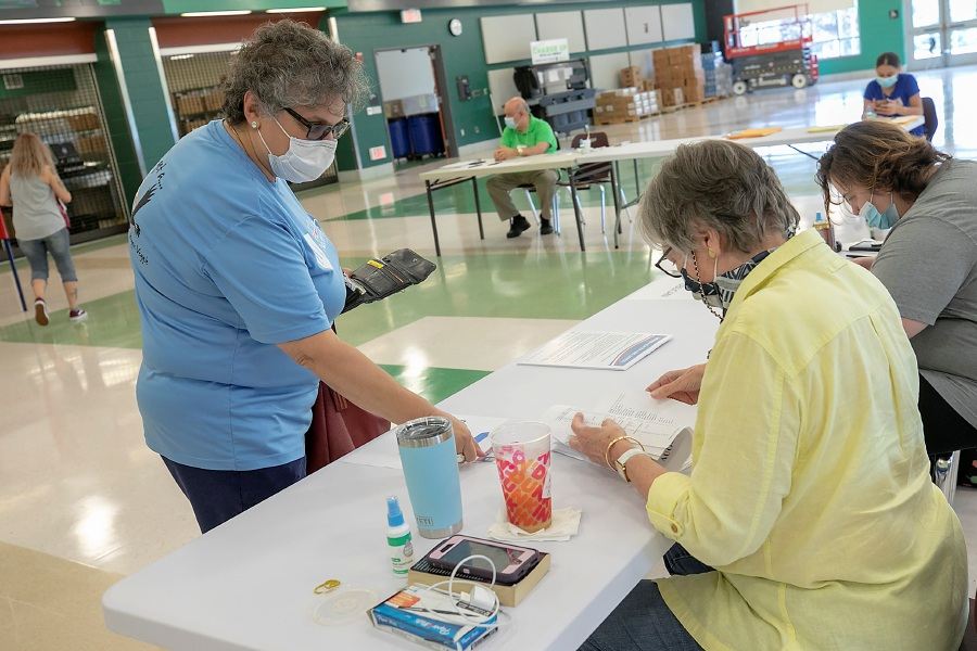 MaryAnn Palmieri, of Meriden, left, is verified by official checker Nancy Young on Tuesday  during primary election day at the Maloney High School polling place.