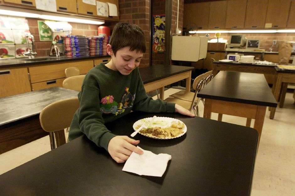 "Worried that he has to finish everything on his plate, sixth grader Jeff Regula stays after class during a ""Greek Day"" smorgasbord at Washington Middle School Jan 12, 2001. His teacher said he did not have to eat it, but he was encouraged to try it. Later Jeff admitted, ""The goat cheese is the only thing I really like...and the noodle stuff."""