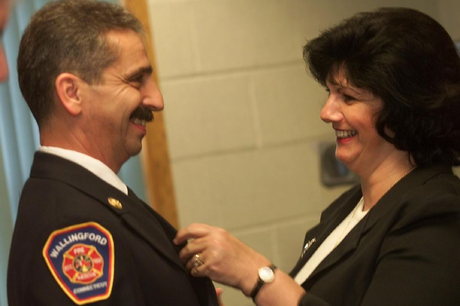 Guy Casanova, left, gets a badge pinned onto his uniform by his wife Carla Casanova, right July 27, 2000. Guy Casanova had just been sworn in as the deputy chief for the Wallingford Fire Department during a ceremony at the Wallingford Fire Headquarters.