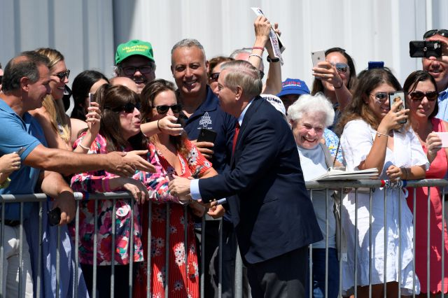 Sen. Lindsey Graham, R-S.C., greets people at Francis S. Gabreski Airport in Westhampton Beach, N.Y., Friday, Aug. 9, 2019, after arriving via Air Force One with President Donald Trump. Trump is in the Hamptons to attend a pair of fundraisers before heading to his golf club in New Jersey for vacation. (AP Photo/Susan Walsh)
