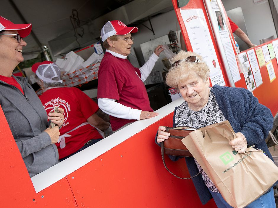 Wanda Thompson, of Plainville, smiles after purchasing 4 bags of apple fritters at the Zion Lutheran Church Apple Fritter Booth in Southington, Tues., Oct. 8, 2019. Volunteers Nancy Benoit, left and Ruth Wilson continue taking orders. Dave Zajac, Record-Journal