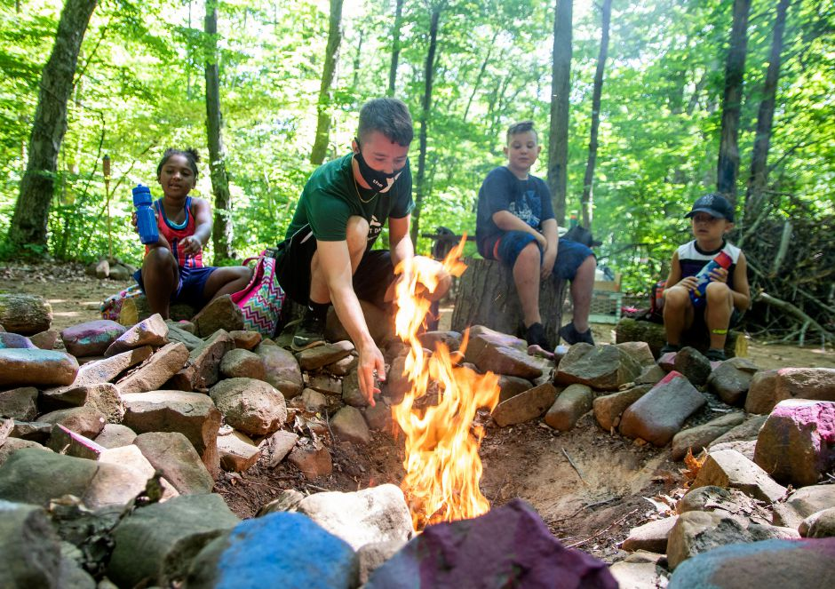 Camp counselor Bryan Brazeo gets a fire started at his group's campground area in the woods at the Meriden YMCA's Mountain Mist Day Camp on Friday. Each group has its own designated camping area where they do their arts and crafts, eat lunch, have campfires and spend time together. Photos by Aaron Flaum, Record-Journal
