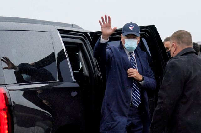 Democratic presidential candidate former Vice President Joe Biden waves as he exits his motorcade to board his campaign plane in New Castle, Del., Friday, Oct. 16, 2020, en route to Detroit. (AP Photo/Carolyn Kaster)