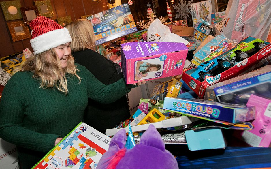Julia Lafond, of Wallingford, left, and her mother, Holly, add donated toys Thursday to a pile of thousands during the annual Toys for Tots donation event at Gaetano's Tavern on Main, 40 N. Main St. in Wallingford. Dave Zajac, Record-Journal