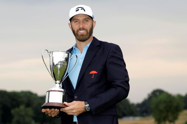 Dustin Johnson poses with the trophy after winning the Travelers Championship golf tournament at TPC River Highlands in Cromwell on June 28, 2020.