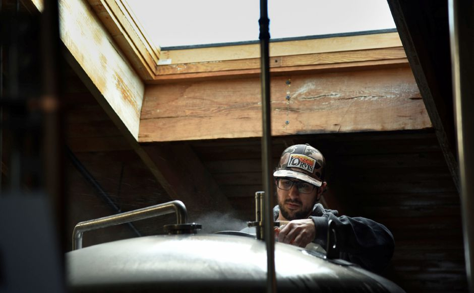 Head Brewer Justin Benvenuto works over a fermenter tank at Kinsmen Brewing Co. in Southington on Jan. 15, 2020. | Bailey Wright, Record-Journal