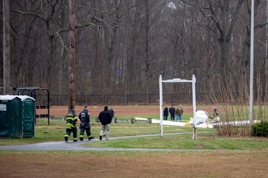 Meriden firefighters walk along the path from Wilcox Technical High School towards the downed plane Friday morning April 12, 2019. | Richie Rathsack, Record-Journal