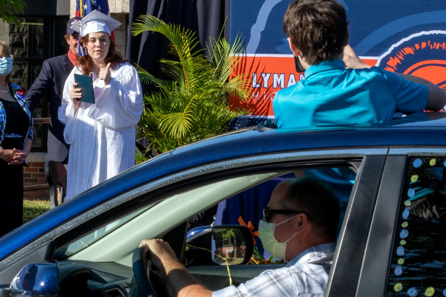 Lyman Hall's graduate Malia Judd gets her photo taken after receiving her diploma Monday Jun22, 2020 during a drive up graduation. Aaron Flaum. Record-Journal
