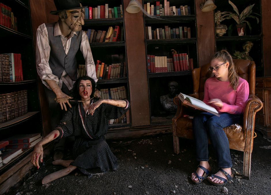 Paige Schmitt, marketing coordinator, looks over a book next to ghoulish figures in a scene at The Haunted Graveyard at Lake Compounce, Fri., Sept. 20, 2019. Dave Zajac, Record-Journal
