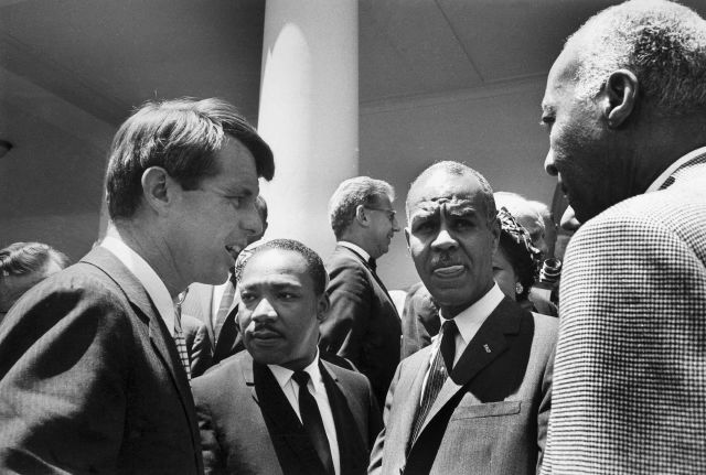 FILE - In this June 22, 1963, file photo, U.S. Attorney General Robert F. Kennedy, left, speaks with civil rights leaders, beginning second from left, Rev. Martin Luther King, Jr., head of the Southern Christian Leadership Conference; Roy Wilkins, executive secretary of the NAACP; and A. Phillip Randolph, president of Brotherhood of Sleeping Car Porters, on the White House grounds, in Washington, DC. Civil rights lawyer Joseph Rauh stands in the background at center. Nearly 50 years after Robert F. Kennedy
