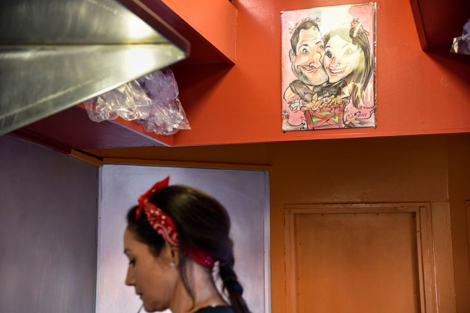 A caricature drawing of Poutine Gourmet partners Kris Barletta and Lisa Greene hangs inside their food truck, while at the Apple Harvest Festival in Southington on Oct. 4, 2019. | Bailey Wright, Record-Journal