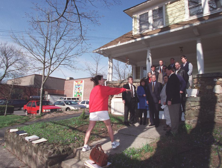 With a camera in hand, YMCA membership marketing director Dina Vernon, arranges Wallingford rotary members and YMCA executives for a photo on the steps of 55 South Elm Street in Wallingford April 13, 2000. The YMCA is buying the property, which is next to the YMCA building, and making it into a teen center.