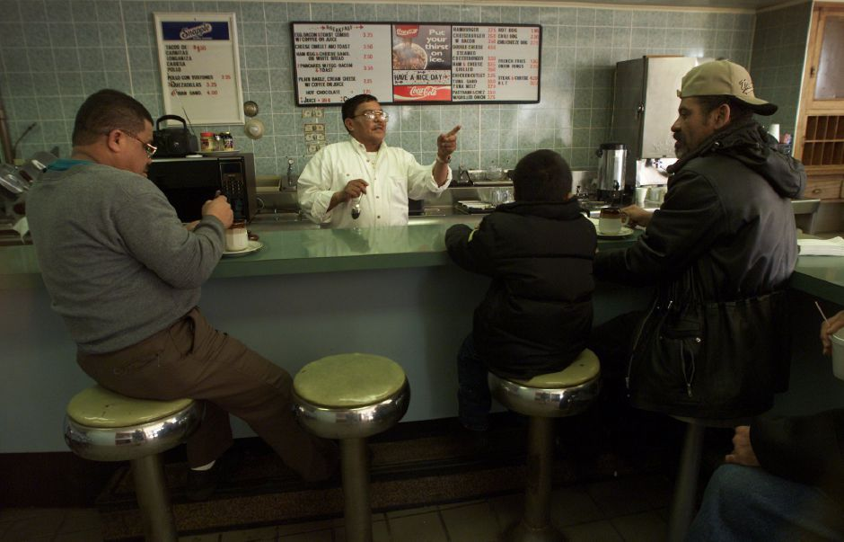Sitting on the stools are Victor Adorno, left, Javier Montero, 4, middle, and his father Juan Adorno, right, all of Meriden, getting lunch at The Jalapeno Restaurant at 62 East Main Street in Meriden Jan. 3, 2001. Behind the counter is Filepe Aquino, father of the owner.