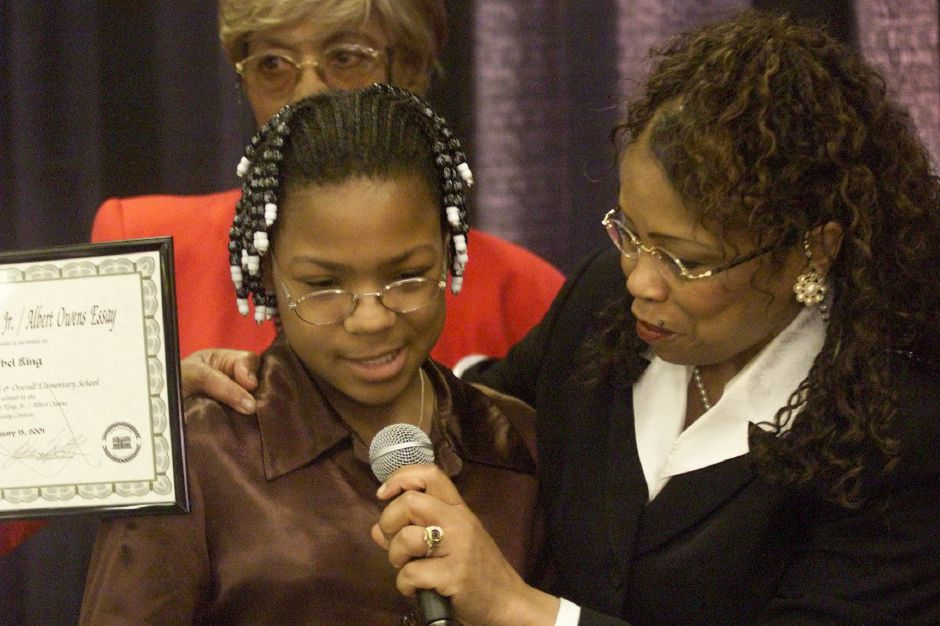 Rachel King, the Elementary School Co-Winner from Roger Sherman School, receiving his Essay Award from Guest Speaker The Honorable Curtissa R. Cofield at the 16th Annual Albert Owens Martin Luther King, Jr. Scholarship Breakfast Mon. morning, Jan. 15, 2001 at Maloney.
