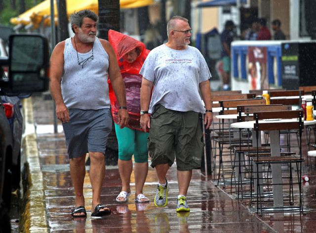 South Beach tourists from Hungary brave the rain as a tropical storm warning was issued for coastal Miami-Dade, Fla., Monday, Sept. 3, 2018. Weather forecasters said the storm could strengthen to near-hurricane force by the time it hits the central U.S. Gulf Coast. (Carl Juste/Miami Herald via AP)