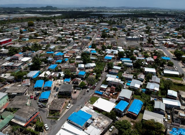 This June 18, 2018 photo shows an aerial view of the Amelia neighborhood in the municipality of Catano, east of San Juan, Puerto Rico. Thousands of people across Puerto Rico are still living in damaged homes, protected by blue plastic tarps, nine months since Hurricane Maria devastated the island. (AP Photo/Dennis M. Rivera)