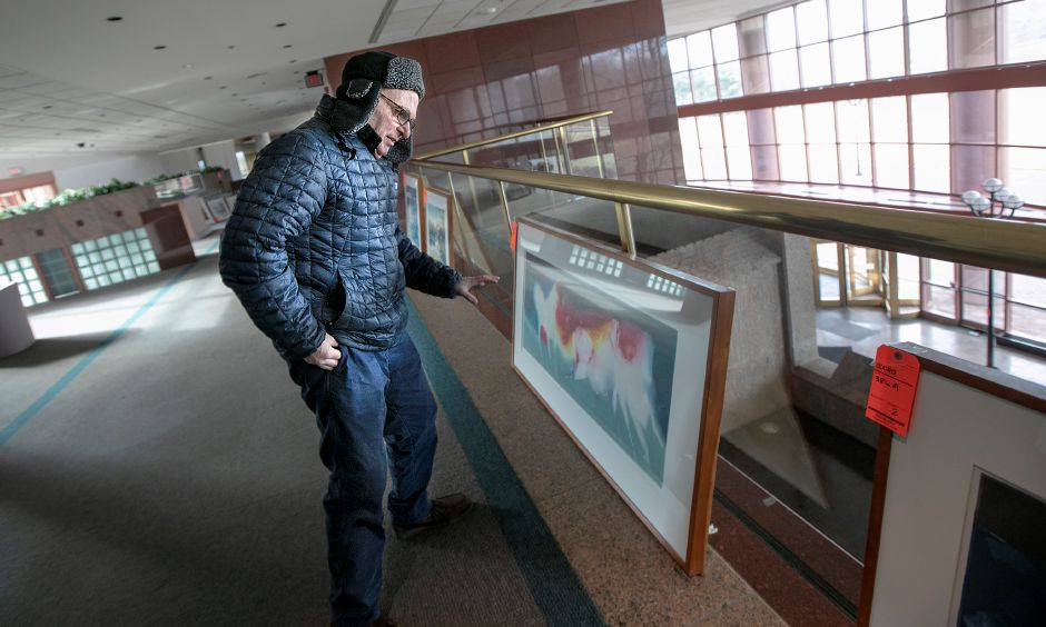 Ken Katz, vice president of evaluations for Enfield based Capital Recovery Group, looks over a painting while tagging artwork for auction in the former Bristol-Myers Squibb in Wallingford, Fri., Jan. 25, 2019. Dave Zajac, Record-Journal