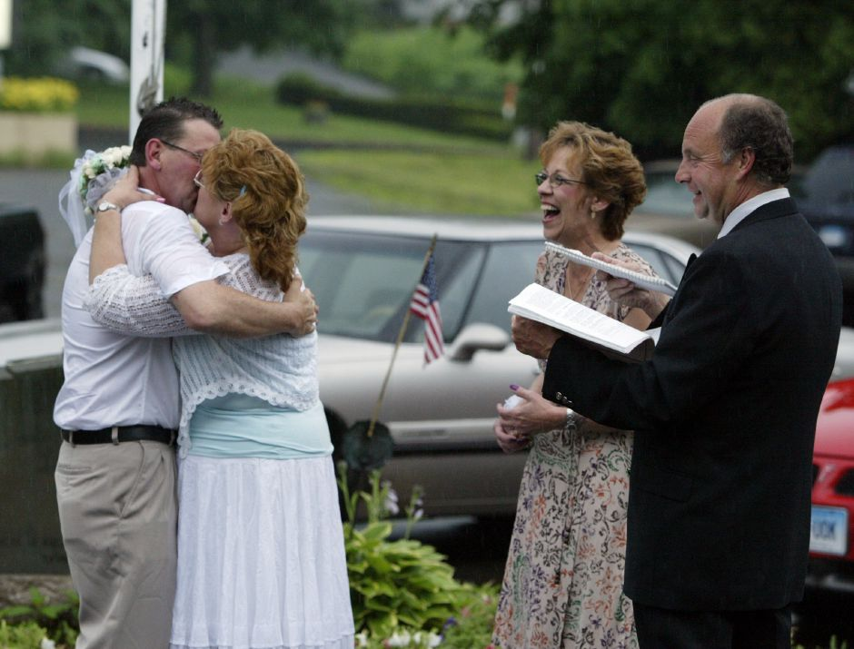 Robert Plourde, left, kisses his wife, Carol Plourde, formerly Tonkowicz, after they were married in the rain by Justice of the Peace John Dalton, right, in front of the American Legion Post 45 in Meriden on June 24, 2006. Robert proposed to Carol on Tuesday, June 20. Carol, not being one to wait, got a marriage license the day after and set up the ceremony for Saturday. Robert is the commander of the Sons of the American Legion and was supposed to be cooking chicken for the Bar-B-Que Chicken Dinner fundraiser at Post 45 that evening. Instead he got married. | File photo