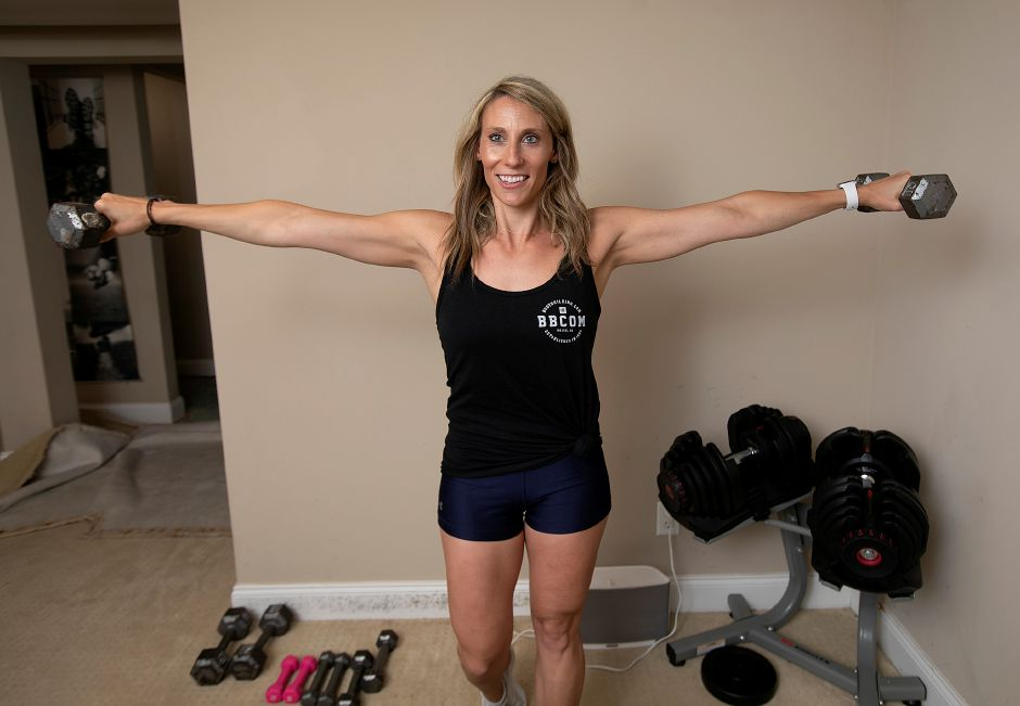 Ann Marie Svogun, of Wallingford, founder of The Fit Blonde LLC, does a few shoulder raises at her residence.
